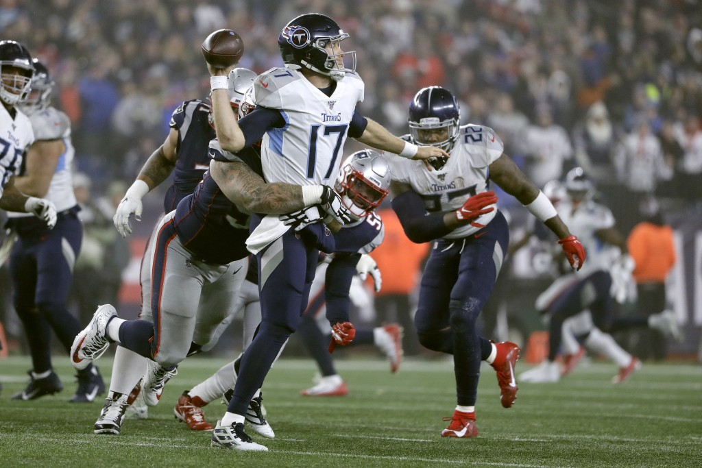 Tennessee Titans quarterback Ryan Tannehill passes while in the grasp of New England Patriots defensive tackle Lawrence Guy in the second half of an N...