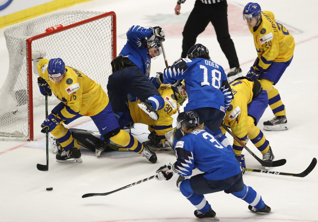 Sweden's Mattias Norlinder, left, controls the puck as players scrum in front of the goal during the U20 Ice Hockey Worlds bronze medal match between ...