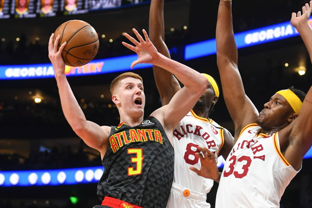 Atlanta Hawks guard Kevin Huerter (3) shoots as Indiana Pacers forward Justin Holiday (8) and center Myles Turner (33) defend during the first half of...