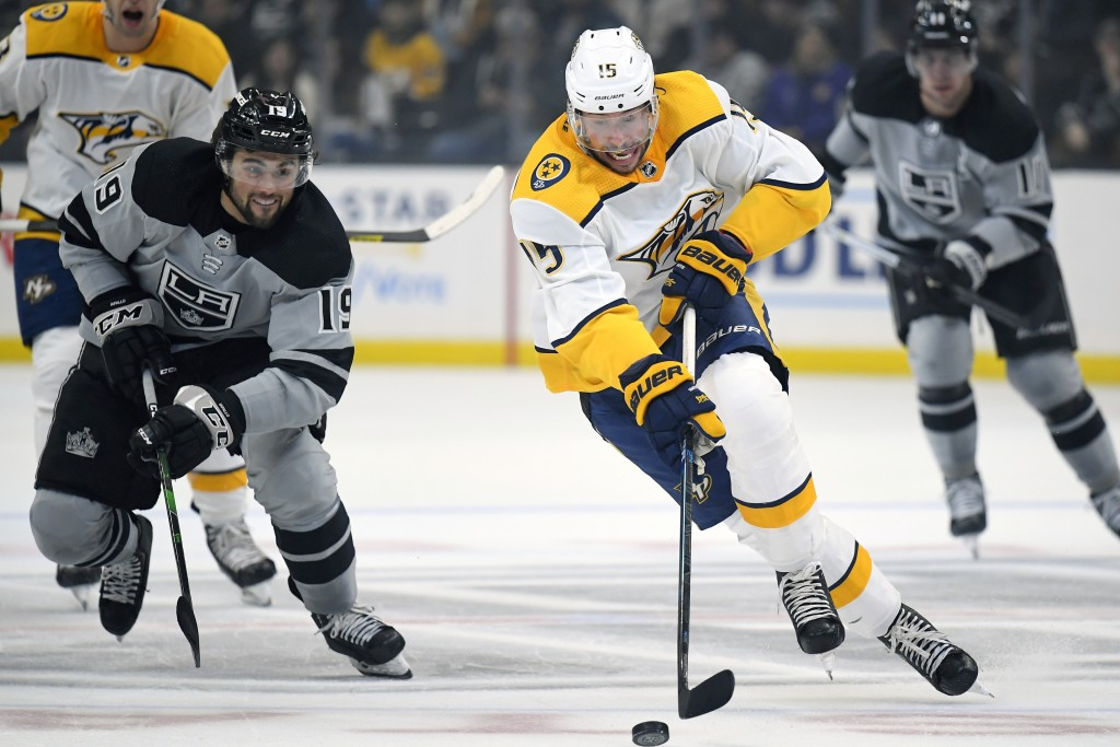 Nashville Predators right wing Craig Smith, right front, moves the puck as Los Angeles Kings left wing Alex Iafallo, left, gives chase during the firs...