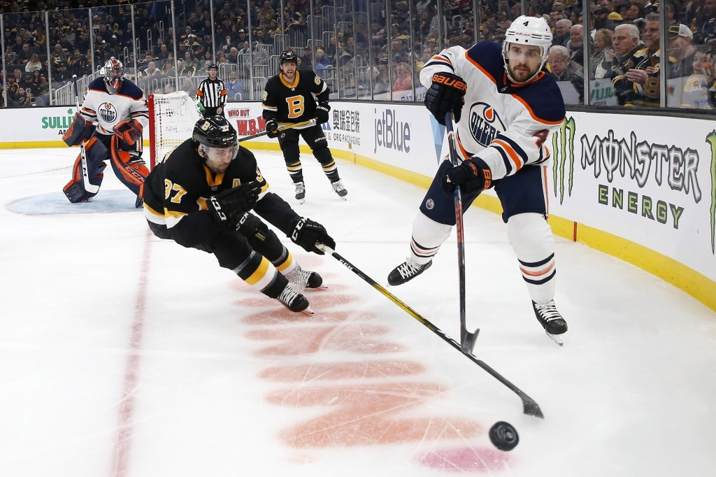 Edmonton Oilers' Kris Russell (4) plays the puck as Boston Bruins' Patrice Bergeron (37) skates in during the first period on an NHL hockey game in Bo...