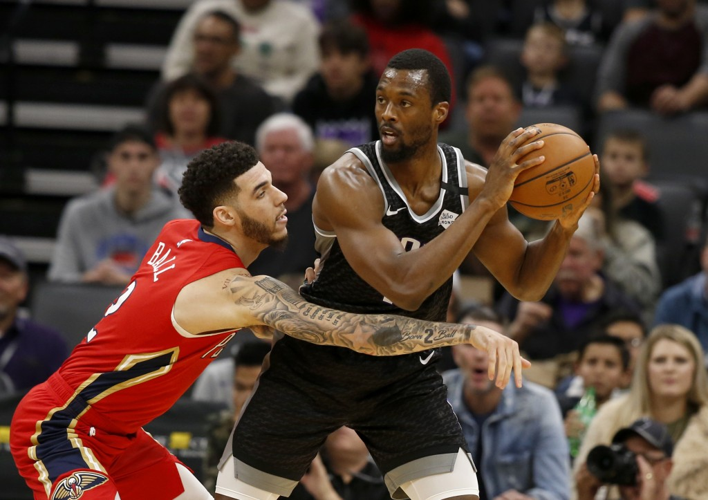 New Orleans Pelicans guard Lonzo Ball, left, reaches for the ball held by Sacramento Kings forward Harrison Barnes during the first quarter of an NBA ...