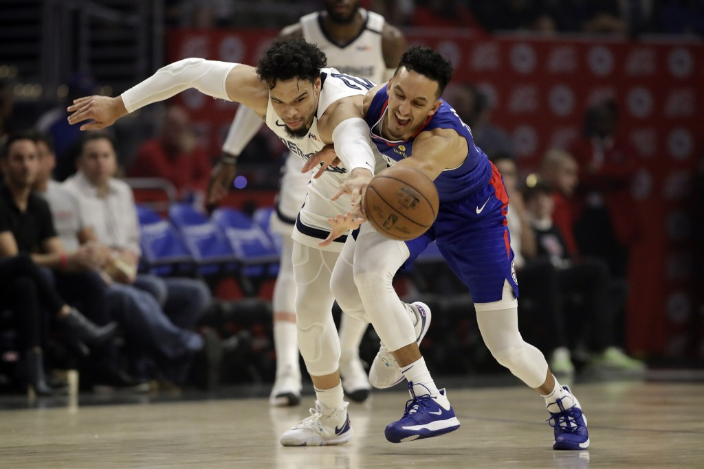 Los Angeles Clippers' Landry Shamet, right, works for a loose ball next to Memphis Grizzlies' Dillon Brooks during the first half of an NBA basketball...