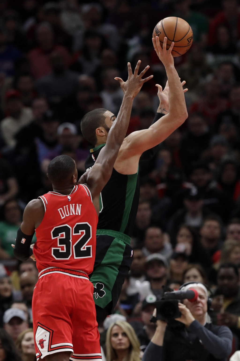 Boston Celtics forward Jayson Tatum, right, goes up for a shot past Chicago Bulls guard Kris Dunn during the first half of an NBA basketball game in C...