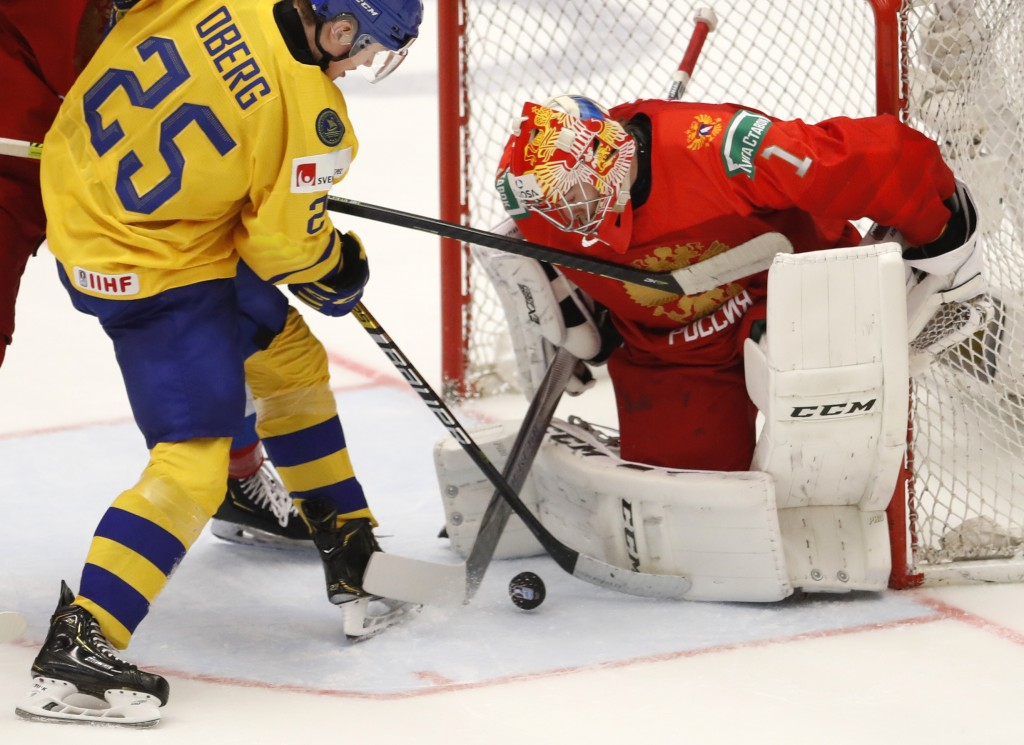 Russia's goaltender Amir Miftakhov, right, makes a save against Sweden's Linus Oberg, left, during the U20 Ice Hockey Worlds semifinal match between S...