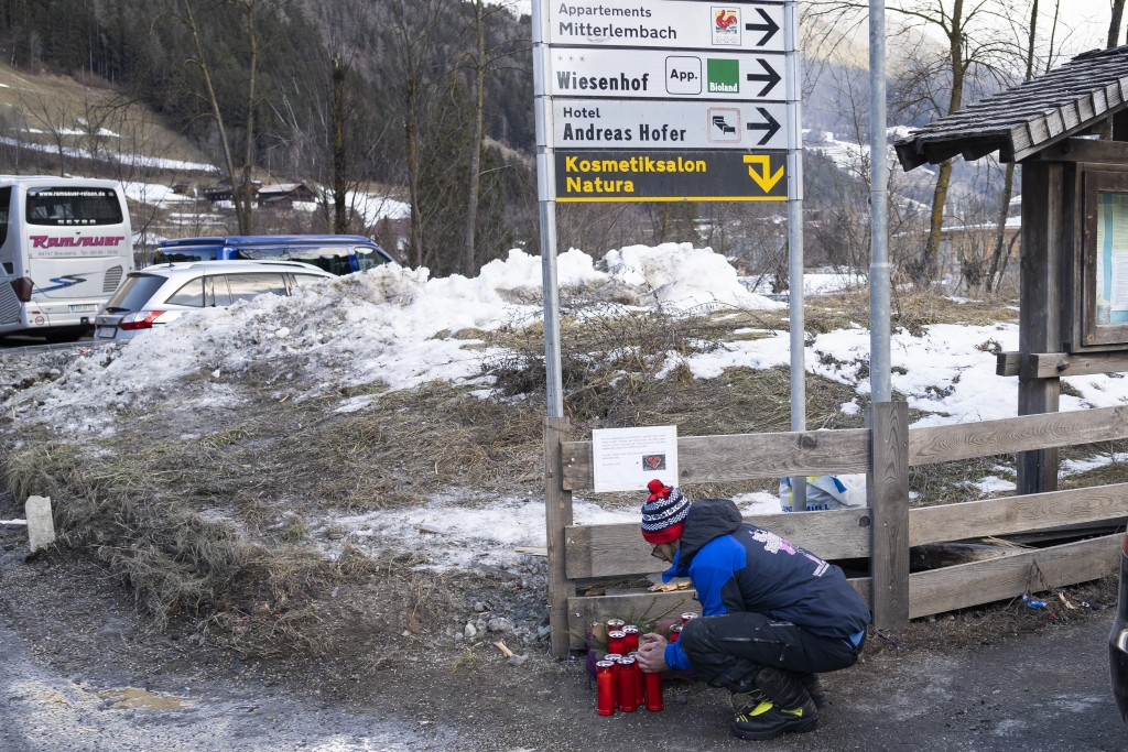 A man lights a candle at the scene where a car has plowed into a group of people in Luttach, near Bruneck in the northern region South Tirol, Italy, S...