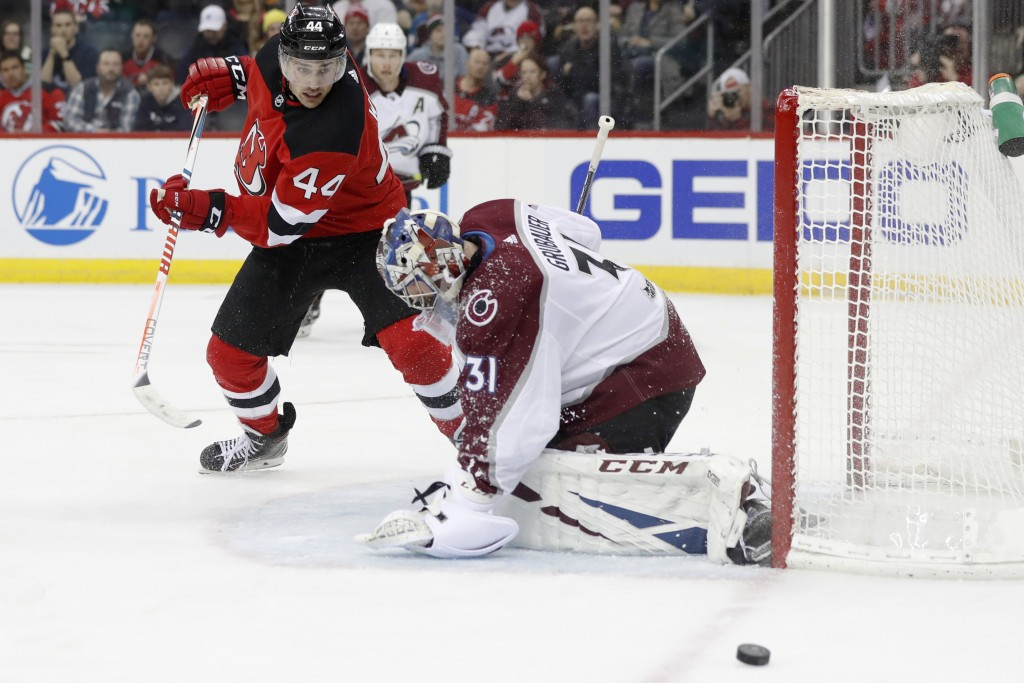 The puck skirts past Colorado Avalanche goaltender Philipp Grubauer (31), of Germany, on a missed scoring chance by New Jersey Devils left wing Miles ...