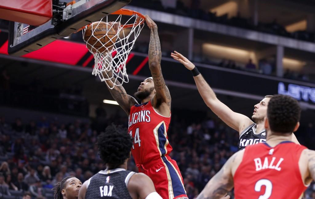 New Orleans Pelicans forward Brandon Ingram, center, dunks between Sacramento Kings' Richaun Holmes, left, and De'Aaron Fox, center, during the first ...