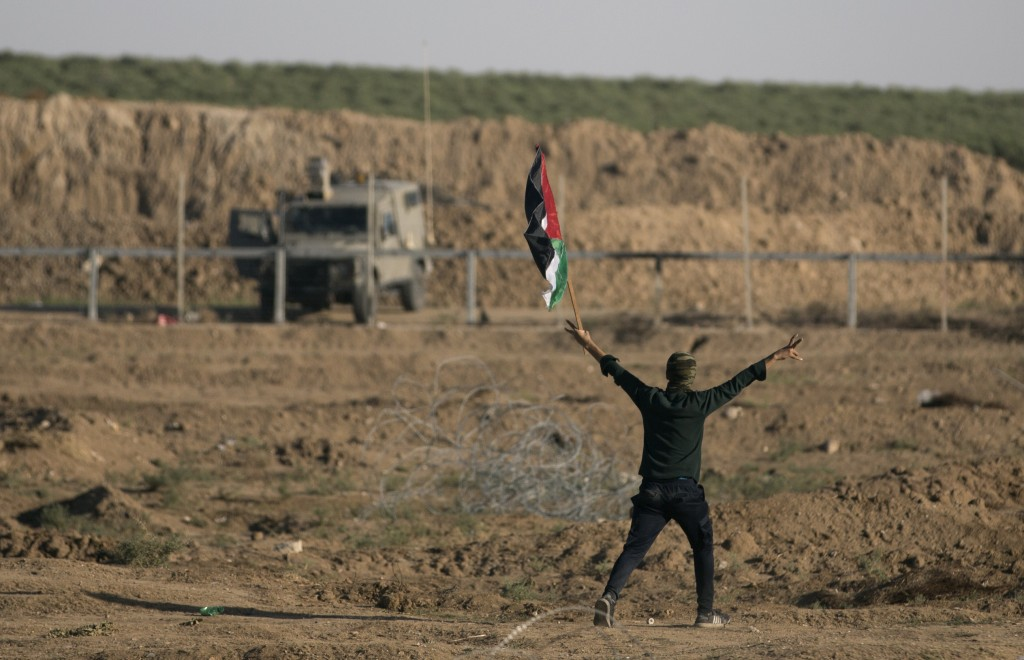 FILE - In this Nov. 2, 2018 file photo, a Palestinian protester flashes the victory sign while holding a national flag during a protest at the Gaza St...