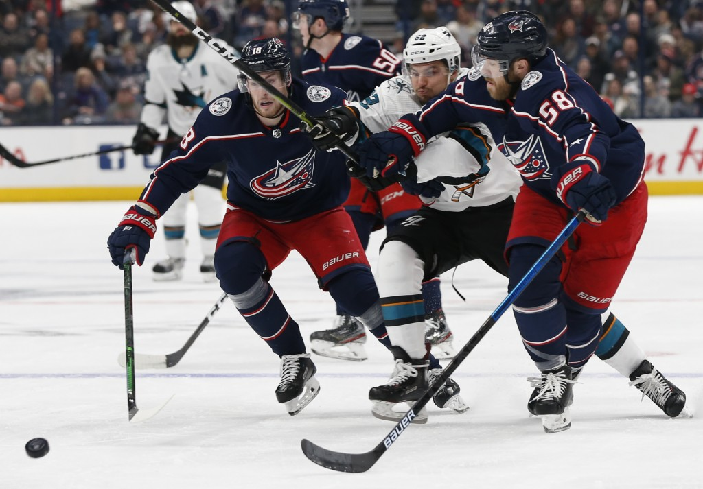 Columbus Blue Jackets' Pierre-Luc Dubois, left, David Savard, right, and San Jose Sharks' Kevin Labanc skate after a loose puck during the first perio...