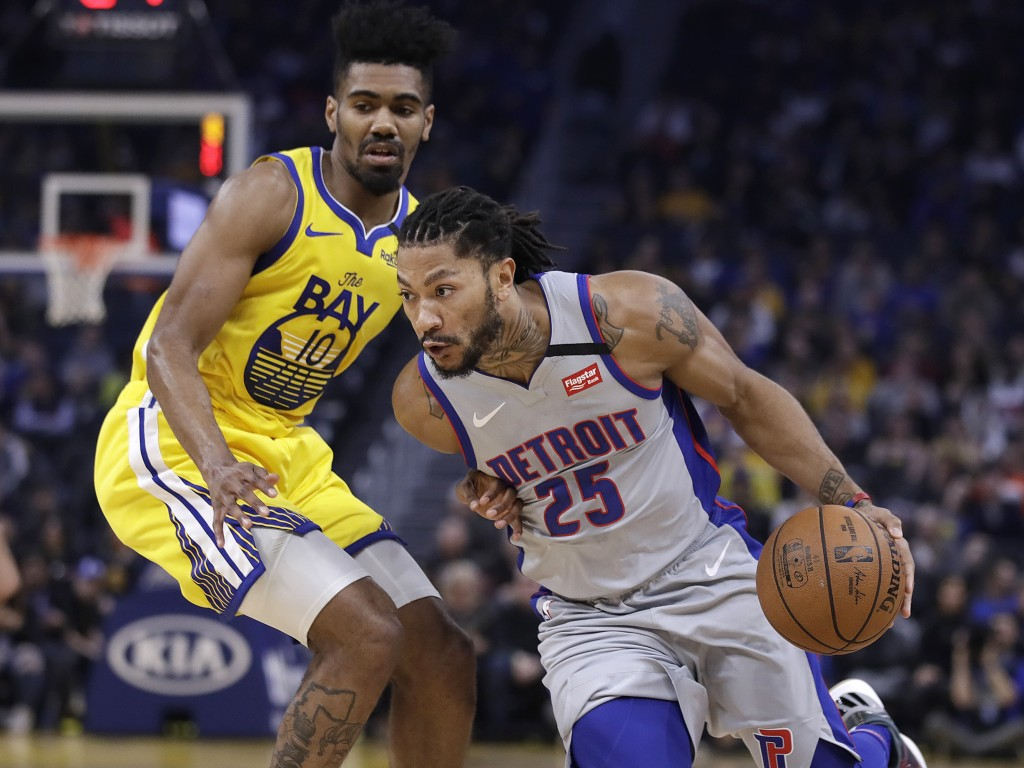 Detroit Pistons' Derrick Rose, right, drives the ball against Golden State Warriors' Jacob Evans (10) during the first half of an NBA basketball game ...