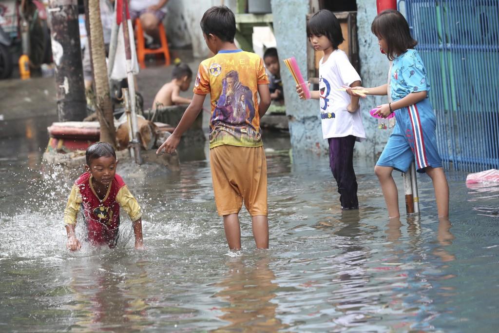 Children play on a flooded street in Jakarta, Indonesia, Sunday, Jan. 5, 2020. Landslides and floods triggered by torrential downpours have left dozen...