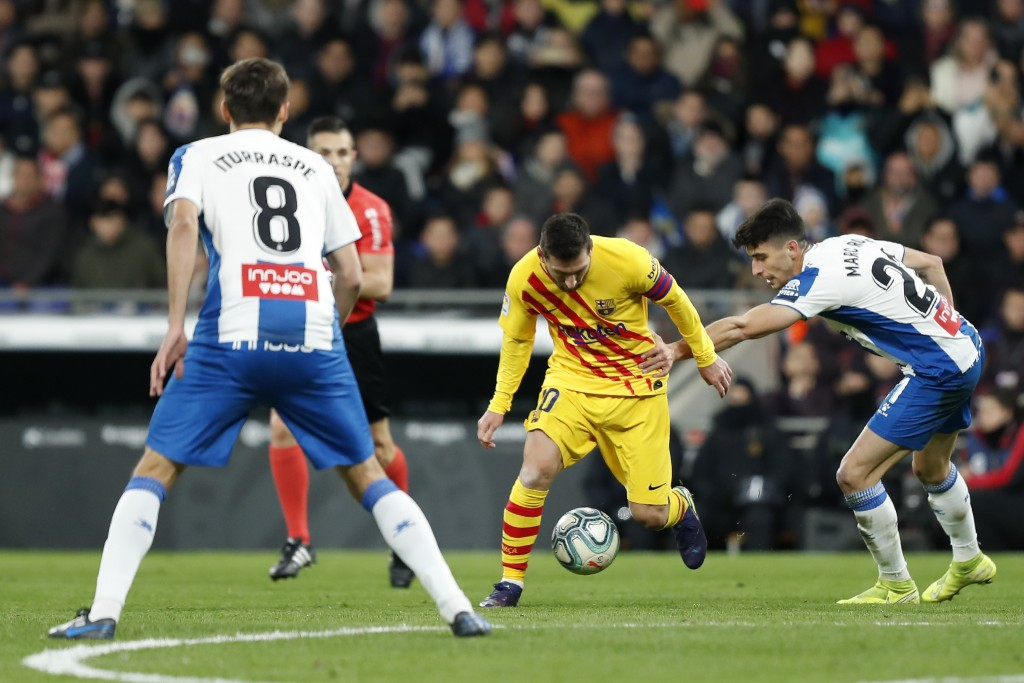 Barcelona's Lionel Messi, center, runs with ball past Espanyol's Marc Roca, right, during the Spanish La Liga soccer match between Espanyol and Barcel...