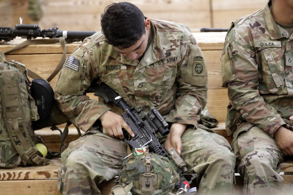 A U.S. Army soldier checks his rifle before heading out Saturday, Jan. 4, 2020 at Fort Bragg, N.C., as troops from the 82nd Airborne are deployed to t...