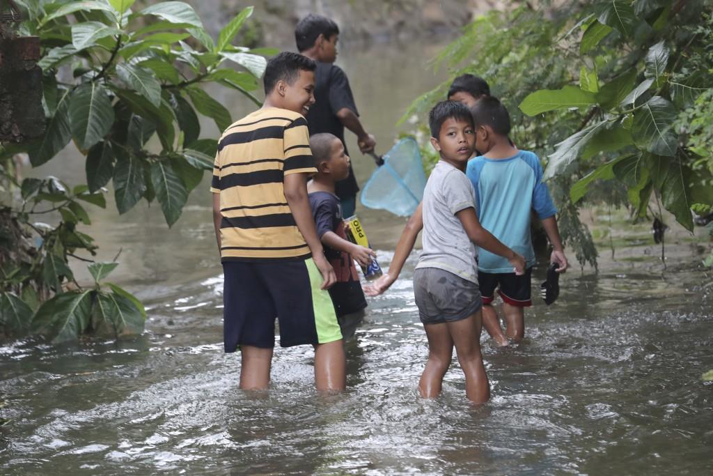Children look for fish after flooded in Jakarta, Indonesia, Sunday, Jan. 5, 2020. Landslides and floods triggered by torrential downpours have left  d...