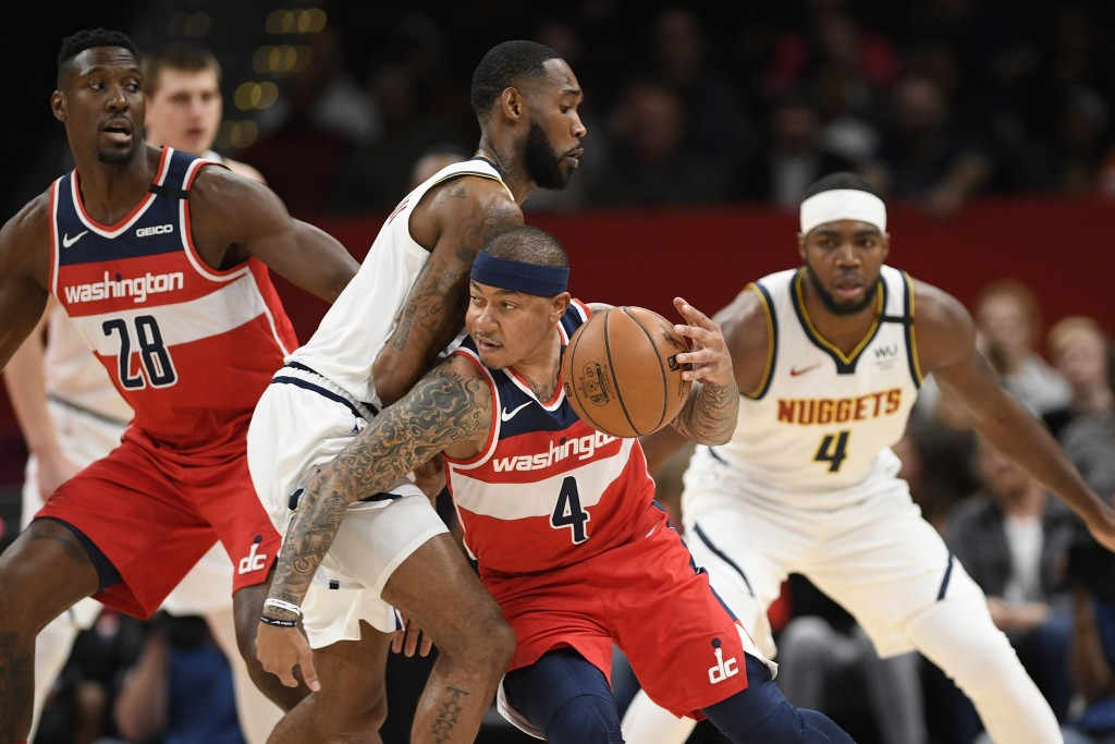 Washington Wizards guard Isaiah Thomas, right center, dribbles the ball next to Denver Nuggets guard Will Barton, left center, during the first half o...