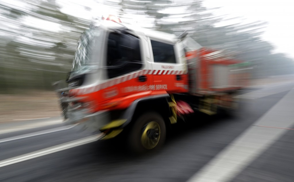 A firetruck races along the road near Nowra, Australia, Sunday, Jan. 5, 2020. The deadly wildfires, which have been raging since September, have alrea...