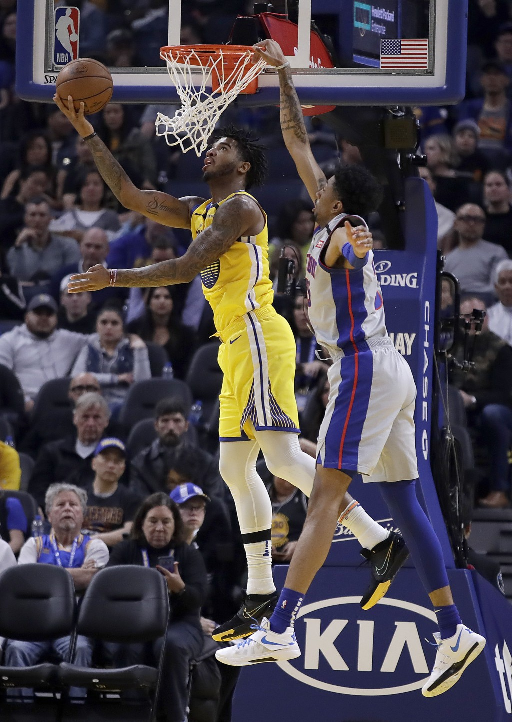 Golden State Warriors' Marquese Chriss, left, lays up a shot against Detroit Pistons' Christian Wood during the first half of an NBA basketball game S...