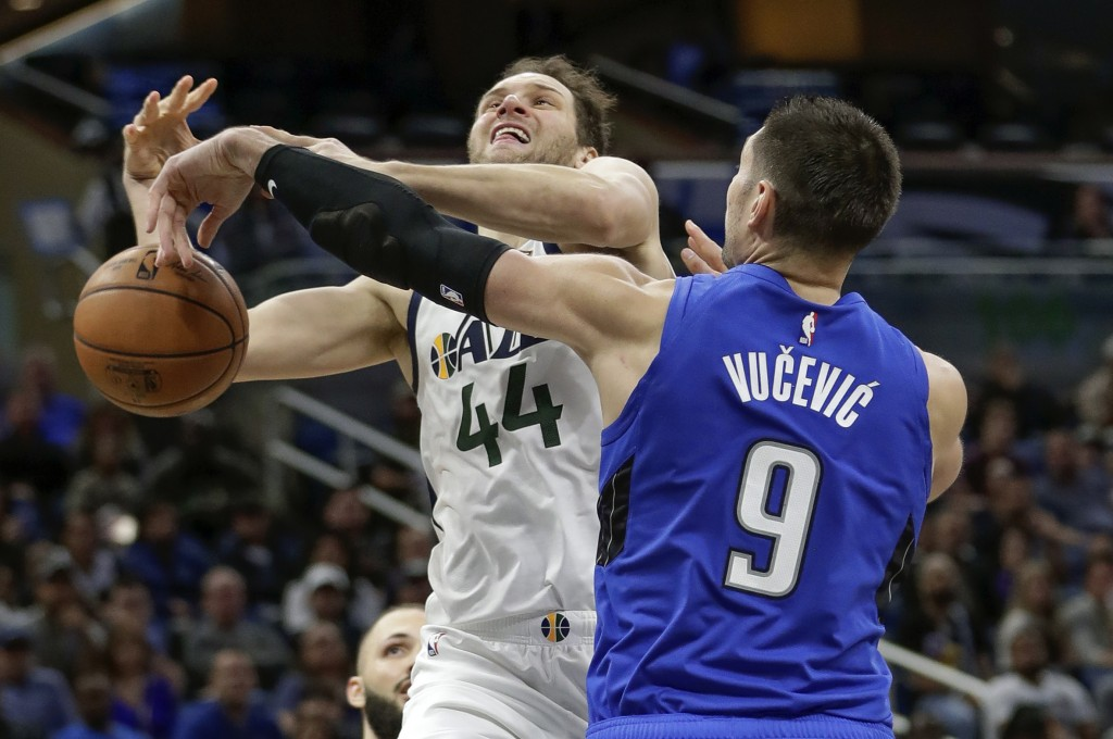 Orlando Magic center Nikola Vucevic (9) knocks the ball out of Utah Jazz forward Bojan Bogdanovic (44) hands as he goes up for a shot during the secon...