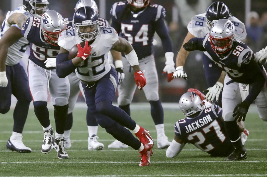 Tennessee Titans running back Derrick Henry runs from New England Patriots defenders in the first half of an NFL wild-card playoff football game, Satu...