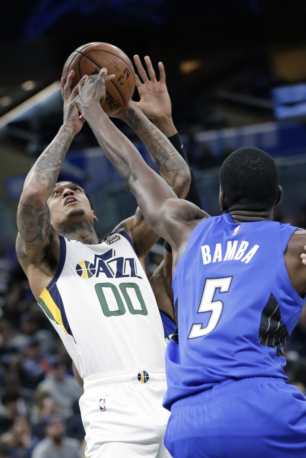 Utah Jazz guard Jordan Clarkson (00) tries to get off a shot over Orlando Magic center Mo Bamba (5) during the second half of an NBA basketball game, ...