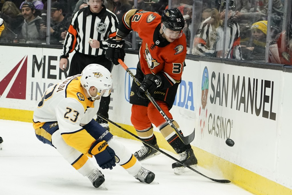 Nashville Predators right wing Rocco Grimaldi, left, and Anaheim Ducks defenseman Jacob Larsson battle for the puckduring the first period of an NHL h...