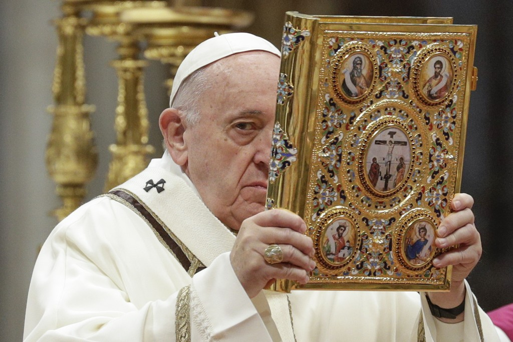 Pope Francis holds up the book of Gospels as he celebrates an Epiphany Mass in St. Peter's Basilica at the Vatican, Monday, Jan. 6, 2020. (AP Photo/An...