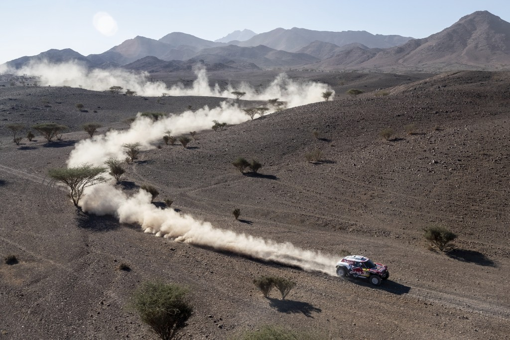 Driver Carlos Sainz, of Spain, and co-driver Lucas Cruz, of Spain, race their Mini during stage two of the Dakar Rally, between Al Wajh and Neom, Saud...