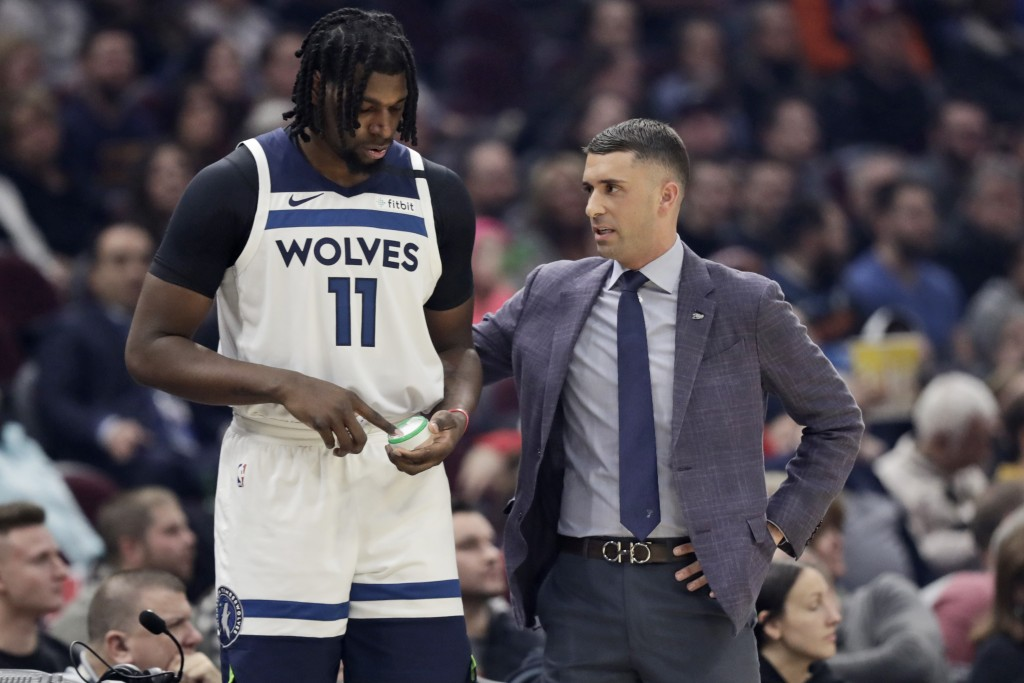 Minnesota Timberwolves head coach Ryan Saunders, right, talks with Naz Reid in the first half of an NBA basketball game against the Cleveland Cavalier...