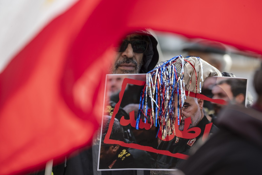 Supporters of the Mujahedeen-e-Khalq, or the MEK, an Iranian exile group, hold signs and flags during a show of support for a U.S. airstrike in Iraq t...