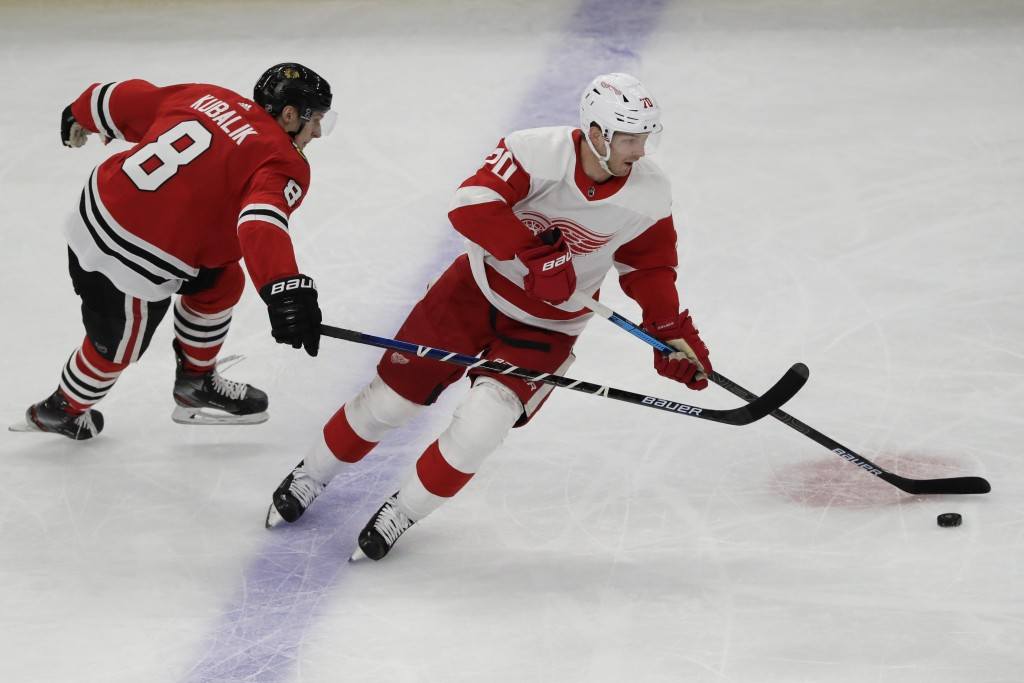 Detroit Red Wings center Christoffer Ehn, right, controls the puck against Chicago Blackhawks left wing Dominik Kubalik during the first period of an ...