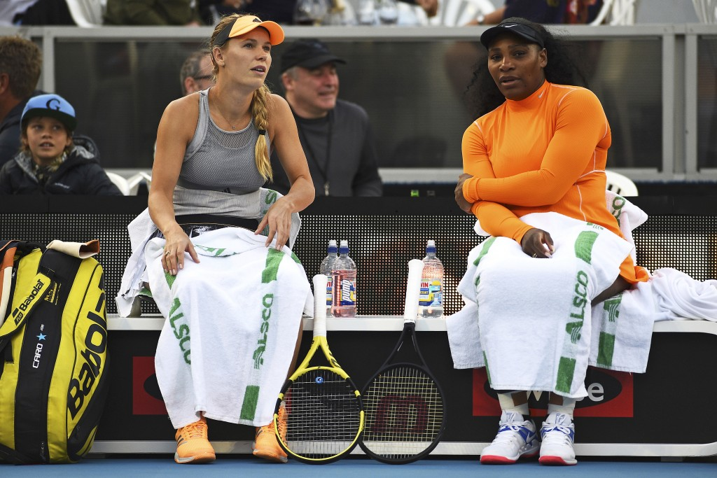 Denmark's Caroline Wozniacki, left, and Untied States' Serena Williams chat during their first round doubles match against Japan's Nao Hibino and Mako...
