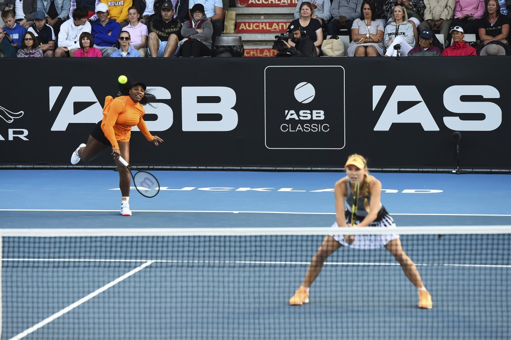 Untied States' Serena Williams, left, serves as Denmark's Caroline Wozniacki looks on during their first round doubles match against Japan's Nao Hibin...