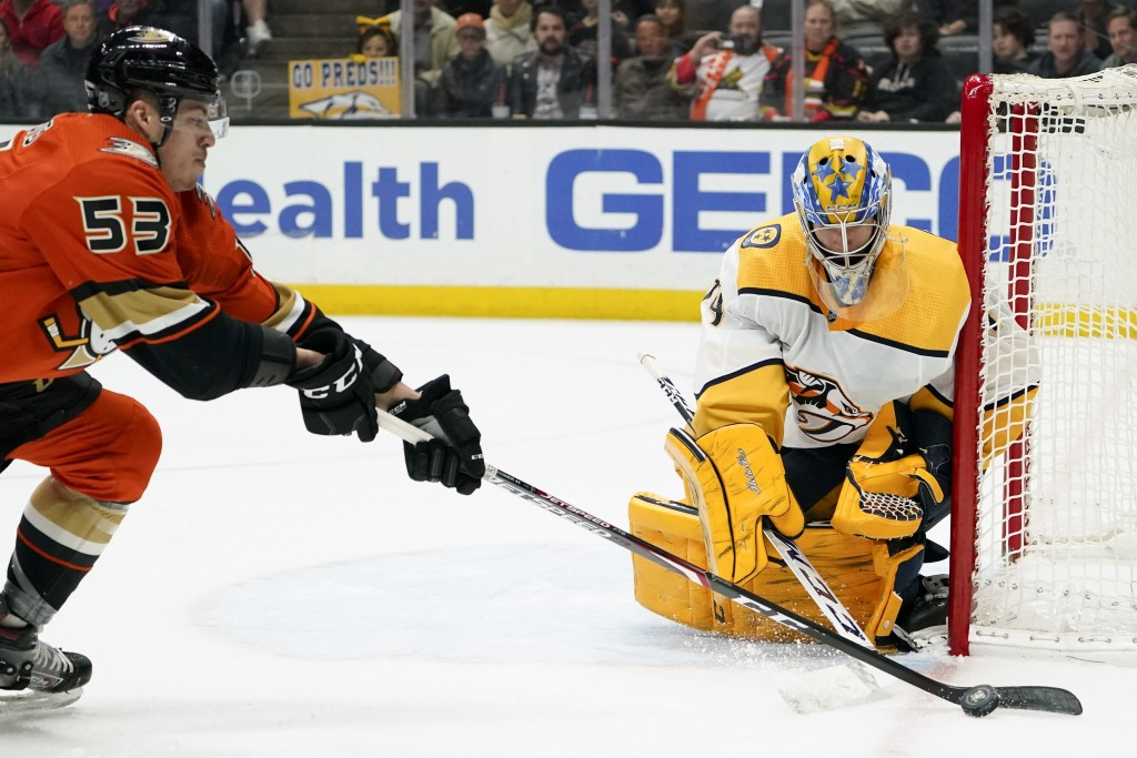 Nashville Predators goaltender Juuse Saros blocks a shot by Anaheim Ducks left wing Max Comtois during the second period of an NHL hockey game in Anah...