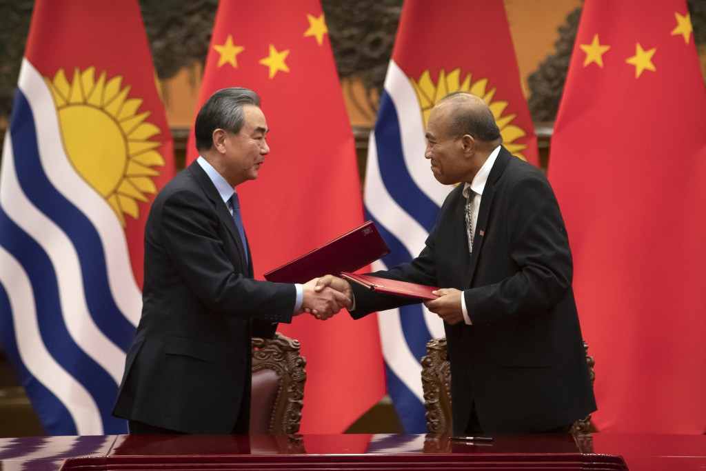 Chinese Foreign Minister Wang Yi, left, and Kiribati's President Taneti Maamau shake hands during a signing ceremony at the Great Hall of the People i...
