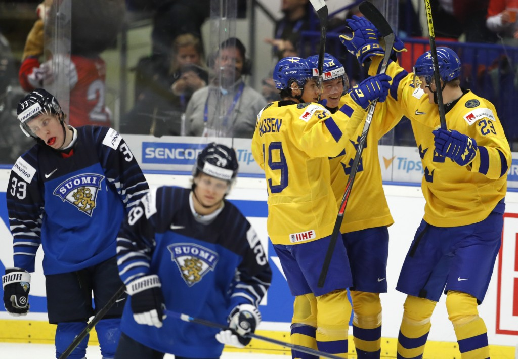 Sweden's Linus Oberg, 2nd right, celebrates with teammates after scoring his sides third goal during the U20 Ice Hockey Worlds bronze medal match betw...