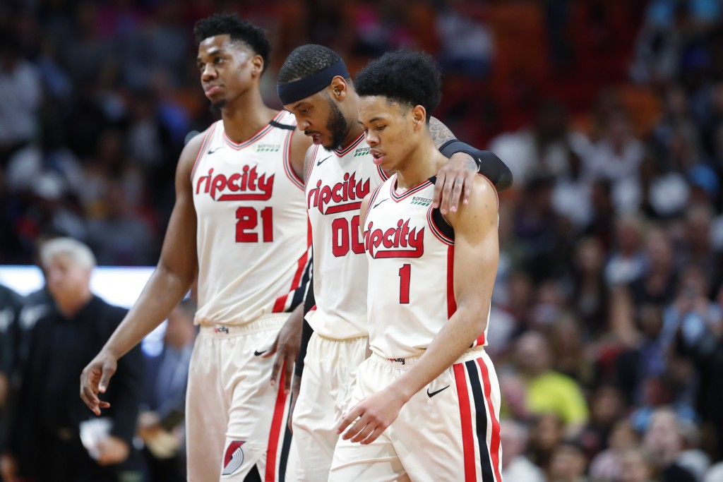 Portland Trail Blazers guard Anfernee Simons (1), forward Carmelo Anthony (00) and center Hassan Whiteside (21) head to the bench during a timeout in ...
