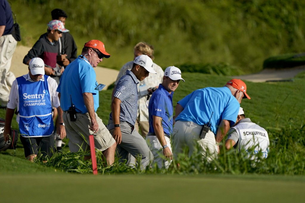 Justin Thomas, center right, and Xander Schauffele, center left, caddies and officials look for Thomas' ball on the 18th hole during final round of th...