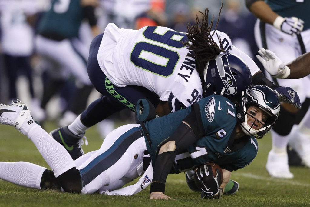 Seattle Seahawks' Jadeveon Clowney (90) hits Philadelphia Eagles' Carson Wentz (11) during the first half of an NFL wild-card playoff football game, S...