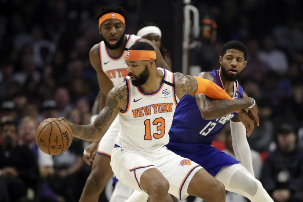 New York Knicks' Marcus Morris Sr., front left, is defended by Los Angeles Clippers' Paul George, right, during the first half of an NBA basketball ga...