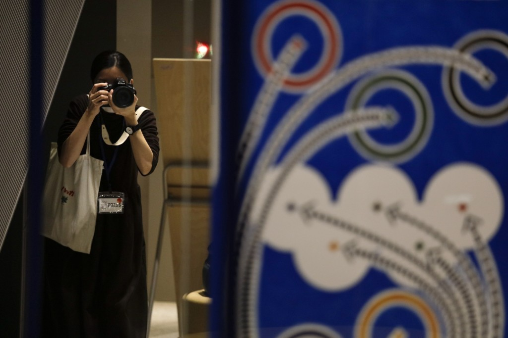 A photographer takes pictures of official posters selected for the Tokyo Olympics and Paralympics, at the Museum of Contemporary Art Tokyo Monday, Jan...