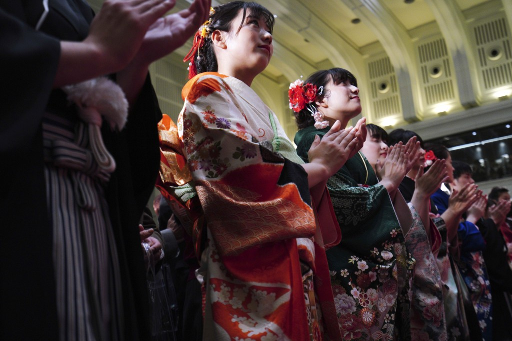Kimono-clad employees of the Tokyo Stock Exchange and models clap during a ceremony marking the start of this year's trading in Tokyo Monday, Jan. 6, ...