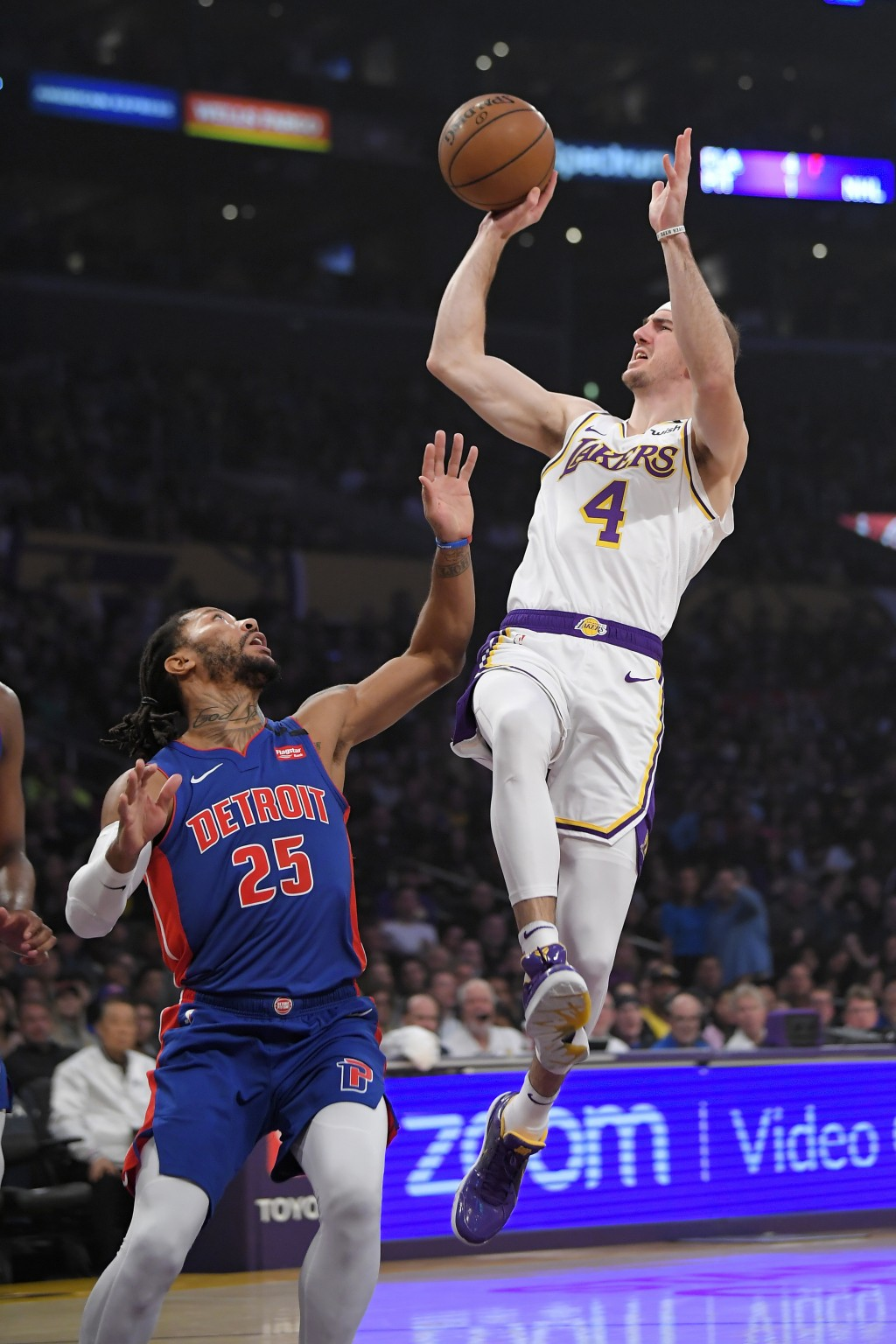 Los Angeles Lakers guard Alex Caruso, right, shoots as Detroit Pistons guard Derrick Rose defends during the first half of an NBA basketball game Sund...