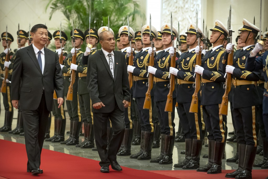 Chinese President Xi Jinping, left, and Kiribati's President Taneti Maamau review an honor guard during a welcome ceremony at the Great Hall of the Pe...