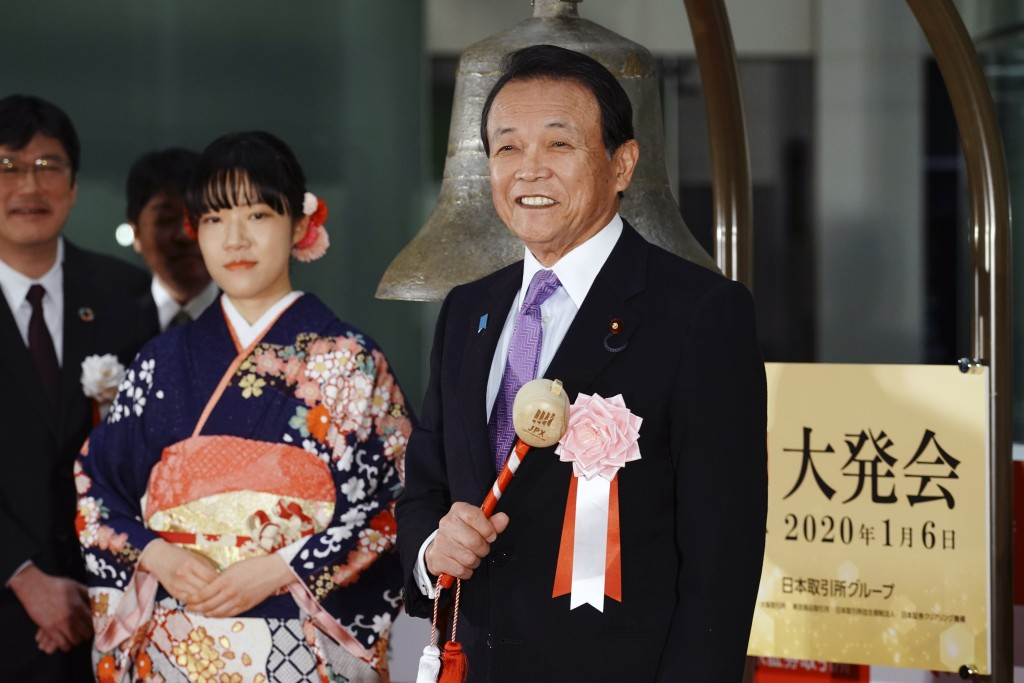 Japan's Finance Minister Taro Aso, right, poses before tolling a bell during a ceremony marking the start of this year's trading in Tokyo Monday, Jan....