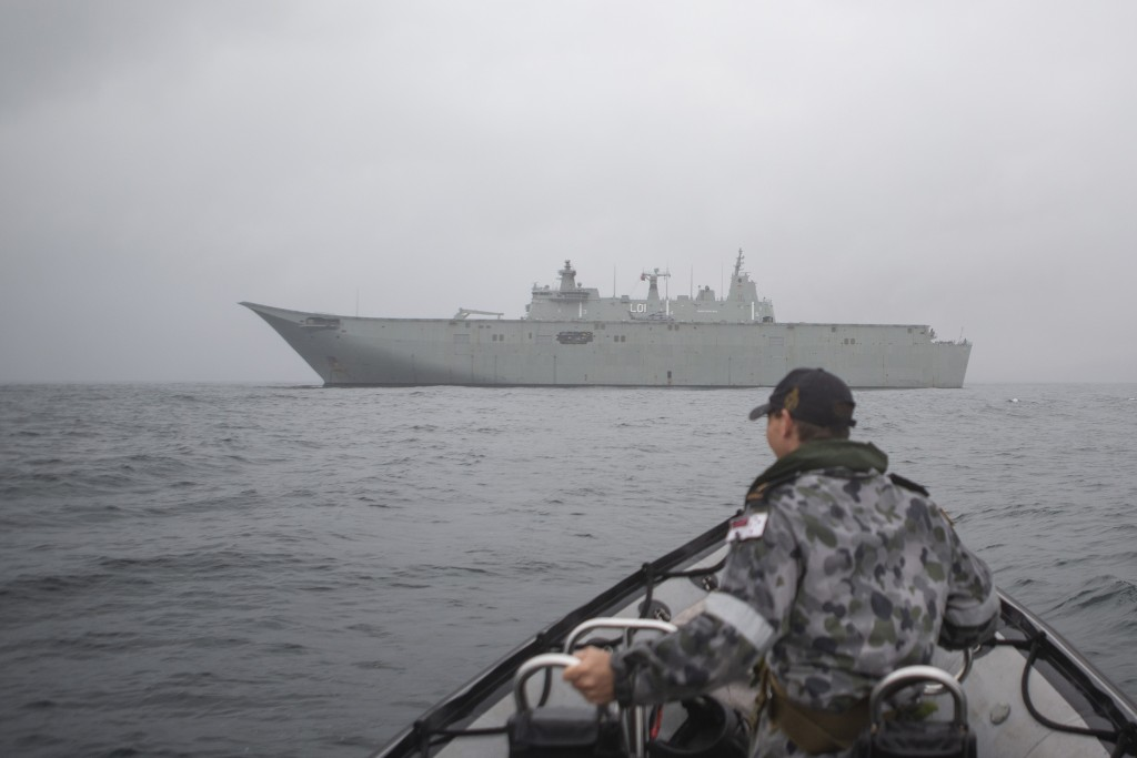 In this photo provided by the Australian Department of Defence on Jan. 6, 2020, HMAS Adelaide is anchored off Eden and is positioned to assist with wi...