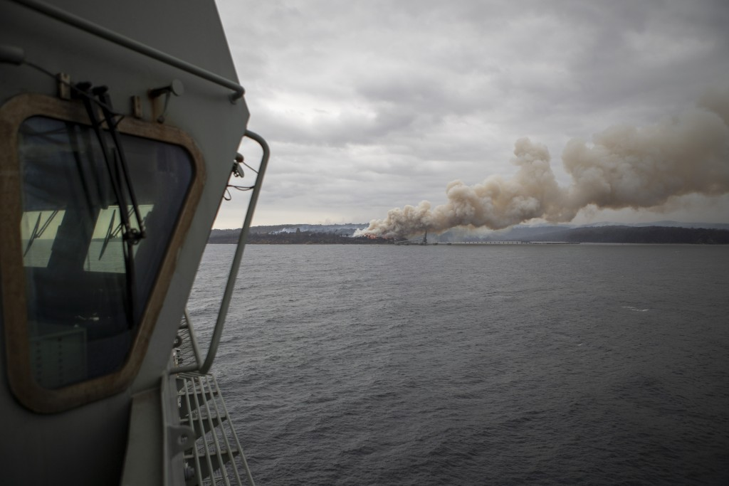 In this photo provided by the Australian Department of Defence on Jan. 6, 2020, a fire burns near Eden as HMAS Adelaide arrives to assist with wildfir...