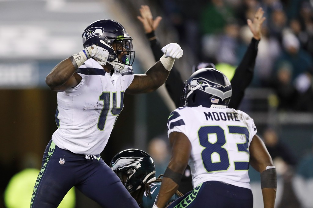 Seattle Seahawks' D.K. Metcalf, left, and David Moore celebrate after Metcalf's touchdown catch during the second half of an NFL wild-card playoff foo...