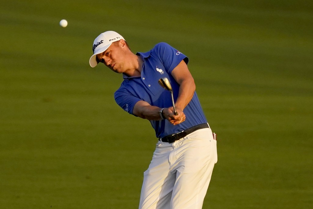 Justin Thomas chips onto the 18th green during the first playoff hole during final round of the Tournament of Champions golf event, Sunday, Jan. 5, 20...