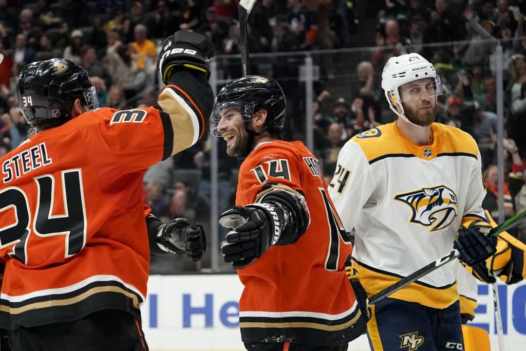 Anaheim Ducks center Adam Henrique, middle, celebrates with center Sam Steel, left, after scoring, as Nashville Predators defenseman Jarred Tinordi sk...